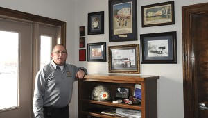 Carriere Volunteer Fire Department Chief Chris Banks stands with the photos and memorabilia of the department history. The department was started in 1972.  Photo by Alexandra Hedrick