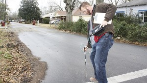 LEAKS: Zack Malley, field supervisor in the city water and gas department, checks for leaks along a gas line after first checking the sewer manhole at the corner of Rowland and Mill streets for the presence of gas.  Photo by Will Sullivan