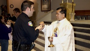 Holy communion: Picayune Police officer Chris Wagner receives holy communion from Father Joseph TruongTrinh. Jodi Marze | Picayune Item