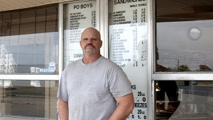 Tim Kellar stands in front his menu and current pricing. The third-generation owner says his philosophy is offering good food and prices the community can afford.  Jodi Marze | Picayune Item