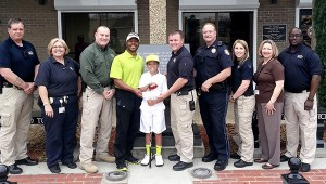 Officers of the Picayune Police Department gathered to present Cameron Guidry with a check to help defray costs of his trip to an international competition. Shown from left are: James Bolton, Theresa Milar, Picayune Police Chief Bryan Dawsey, Cory Guidry with his son Cameron Guidry, Lane Pittman, Gary Wilton, Christa Groom, Ginger Bennett and Lamar Thompson. Jodi Marze   Picayune Item