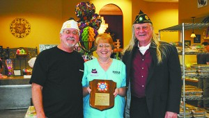 KINDNESS HONORED: From left, Ronald Lowe, quartermaster of the Veterans of Foreign Wars, and Larry Kitts, commander of  VFW and vice-commander of the American Legion, present Sherri Thigpen, owner of Paul's Pastry holding her plaque of appreciation. Photo by Alexandra Hedrick