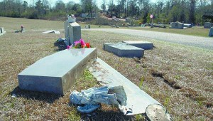 SETTING IT RIGHT: Employees with Magnolia Monument Company reset grave stones knocked over by an unknown suspect Thursday night. About seven grave stones were knocked over by the vehicle at the First Baptist Church of Carriere.