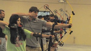 AIM AND FIRE: Students on the Picayune High School Archery competition team finds their target and prepares to fire at targets at practice on Thursday at the Picayune High School Community Safe Room.