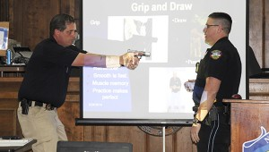 Get a grip: From left: Picayune Police Department Capt. James Bolton demonstrates to the class the proper way to draw and grip their weapons while Patrolman Marcus Whitfield explains the techniques Bolton is using.  Jodi Marze | Picayune Item