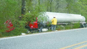 Emergency personnel work to drag this 18-wheeler from the woods Tuesday afternoon.