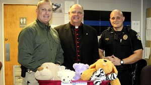 FOR THE CHILDREN:  Canon Jon Filkins continues his efforts to collect stuffed animals to distribute to children in crisis through the Picayune Police Department. Shown from left are Picayune Police Chief Bryan Dawsey, Canon Jon Filkins and Lt. Daniel Davis. Jodi Marze | Picayune Item