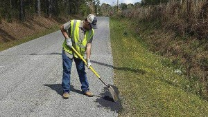 FILLING IN THE HOLES: A member of the Pearl River County Road Department works on fixing a pothole Tuesday afternoon. Both the county road department and Poplarville Public Works have seen an increase in potholes this year.  Photo submitted.