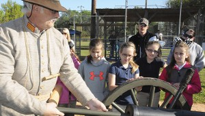LOADING: Pearl River Central Upper Elementary fourth graders watch as Daryl Ladner, a member of the Seven Stars Artillery re-enactment group, loads the cannon with four ounces of black powder.  Photo by Alexandra Hedrick